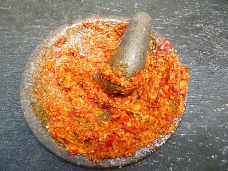 sambal: close up of a stone bowl of sambal chili sauce