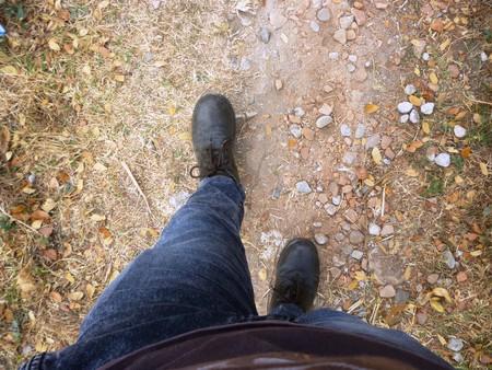 zapatos de seguridad: hombre caminando en la acera, zapatos de seguridad de primer plano Foto de archivo