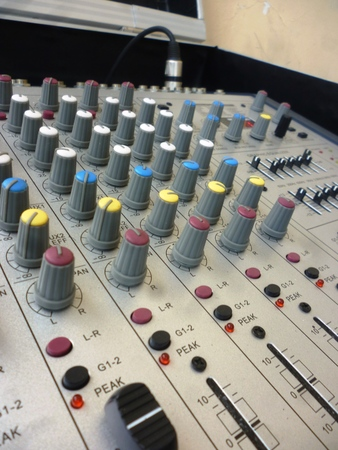 desired: closeup on a sliders of a mixing console. It is used for audio signals modifications to achieve the desired output. Applied in recording studios, broadcasting, television and film post-production