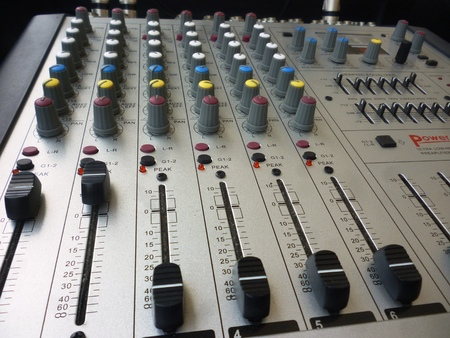 closeup on a sliders of a mixing console. It is used for audio signals modifications to achieve the desired output. Applied in recording studios, broadcasting, television and film post-production