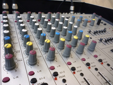 postproduction: closeup on a sliders of a mixing console. It is used for audio signals modifications to achieve the desired output. Applied in recording studios, broadcasting, television and film post-production