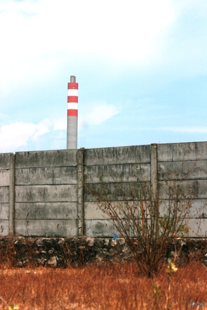 An old factory chimney over a blue sky Stock Photo