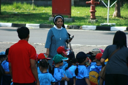 godly: Christian faith nun in action: christian nun and sons outdoors devotional. Godly relationship in a small Hispanic grup. Woman and child kneel, in indonesia, asian