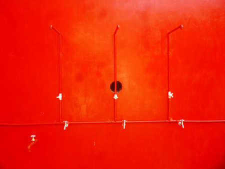 water flows: Water flows from a tap on a red background