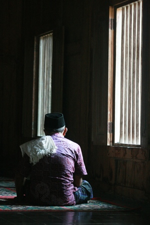 sidelight: An unidentified muslim man prays in  Masjid Mosque in Ki Ageng Selo Graveyeard. Muslim religion is still increasing across the whole Indonesia