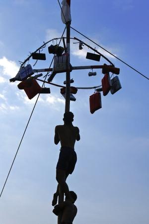 mannelijke uitdrukking in Indonesische bamboepaal klimend nat glad voor prijzen in een ceremonie ter herdenking van de Indonesische onafhankelijkheidsdag elke augustus