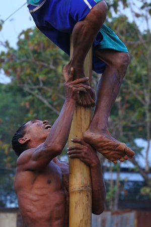 man expression in Indonesian bamboo pole climbing wet slippery for prizes in a ceremony commemorating the Indonesian Independence Day every August Editorial