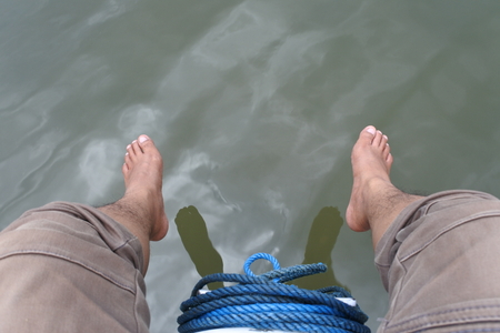 feet dangling over the boat