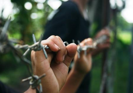 Mains sur gros plan de fil de fer barbelé