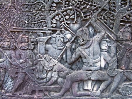 A victorious Khmer warrior deals the death blow to an enemy soldier.