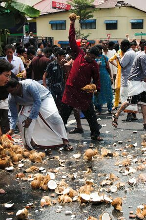 Penang, Malaysia, Feb 2 2009. Devotees smashing coconuts in the street in anticipation of the arrival of Lord Murugans chariot in the annual Thaipusam festival.