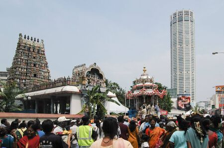 Penang, Malaysia, Feb 2 2009.  In the backdrop of Penangs iconic KOMTAR (Kompleks Tunku Abdul Rahman) building, the silver chariot of Murugan makes a stop in front of the Nagaratha Sivan Temple to receive offerings from devotees.