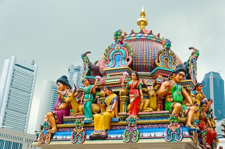 The colourful roof of the Sri Mariamman Temple stands in bright contrast to the skyscrapers of Singapore. Stock Photo