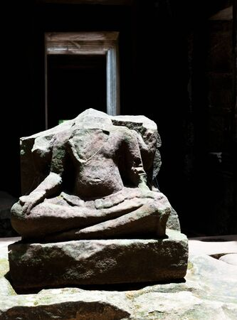 looting: A Buddha, head stolen by treasure hunters, sits silently in a chamber in Angkor.