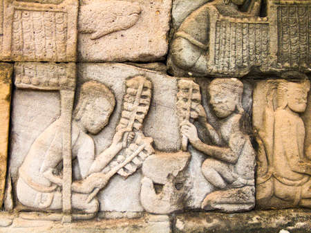 Relief in the walls of the Bayon depicting two men cooking over a stove-pot. photo