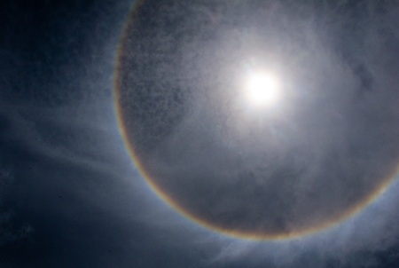 A rare halo forming around the sun at midday Stock Photo