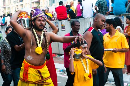 20 January 2011, Kuala Lumpur, Malaysia: A son leads his father as they carry offerings of sweet milk at the annual Thaipusam festival. Editorial