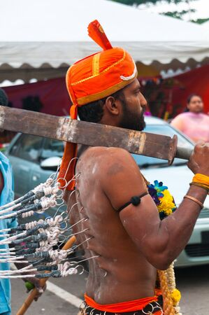hypnotise: 20 January 2011, Kuala Lumpur, Malaysia: In a trance state, this  Hindu devotee is prevented from running wildly from ropes attached to his body by hooks in his flesh. He is thought to be possessed by a deity during the annual Thaipusam festival.