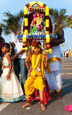 20 January 2011, Kuala Lumpur, Malaysia: A young boy devotee takes a break while carrying the ceremonial kavadi as part of a thanksgiving ritual at the annual Thaipusam festival.