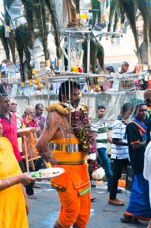 20 January 2011, Kuala Lumpur, Malaysia: A man carrys the ceremonial kavadi, a decorated metal frame, as part of a thanksgiving ritual at the annual Thaipusam festival.