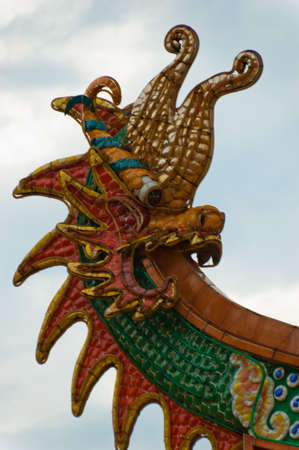 A tiled dragon decoration on the roof of a Chinese temple. Stock Photo