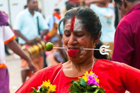 20 January 2011, Kuala Lumpur, Malaysia: A female Hindu devotee is skewered through the cheeks during the annual Thaipusam festival.