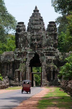 A tuk tuk exits through the gigantic face tower of Angkor Thom. Stock Photo