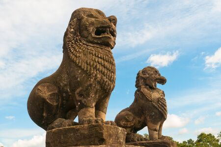 Lion sculptures standing guard over ruins. Stock Photo