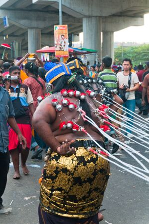 20 January 2011, Kuala Lumpur, Malaysia: Two Hindu devotees, their backs skewered with hooks, are held at bay with ropes at the annual Thaipusam festival.