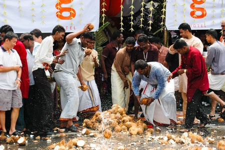 Penang, Malaysia, 2 Feb 2009. A group of Indian men smashing coconuts in the street as part of the annual Thaipusam festival. Editorial