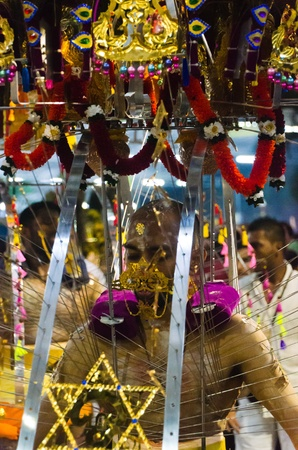 7 February 2012, Singapore: A man carries and is skewered by the ceremonial kavadi, a decorated metal frame, as part of a thanksgiving ritual at the annual Thaipusam festival.