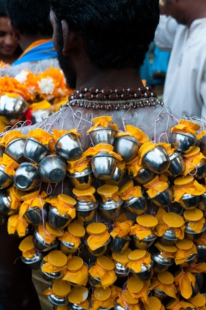 20 January 2011, Kuala Lumpur, Malaysia:  Hindu devotees carrying miniature milk pots on hooks embedded in their backs as part of the Thaipusam festival.