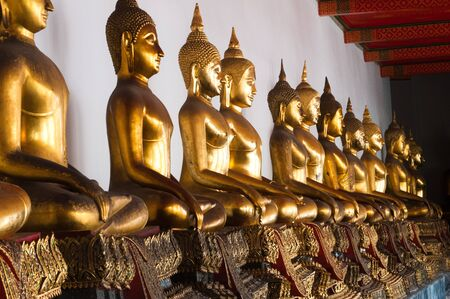 A line of Buddha statues in a Thai temple photo