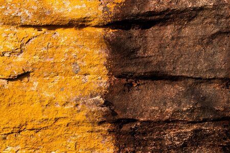 Closeup of a duo-toned rock wall, coloured orange and brown  Stock Photo