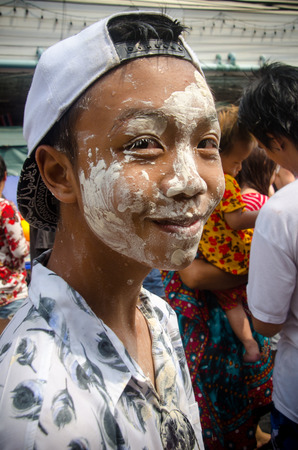 prank: Bangkok, Thailand, 14 April 2015. A Thai festival goer with his face smeared with clay. During the annual Songkran festival, people smear clay on each others face as a prank. Editorial