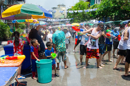 prank: Bangkok, Thailand, 14 April 2015. Groups of partygoers splahs water at each other using water guns, buckets and hoses. The annual Songkran water festival is marked by splashing water on each other.