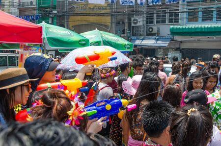 Bangkok, Thailand, 14 April 2015. Women partygoers shooting water guns at the Songkran street party in Khao San Road. The annual Songkran water festival is marked by splashing water on each other.