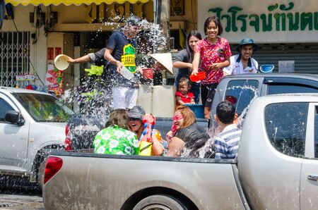 Bangkok, Thailand, 14 April 2015. Groups of festival goers celebrate Songkran by tossing buckets of water on each other while riding on the backs of trucks. The annual Songkran water festival is marked by splashing water on each other.