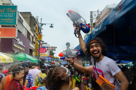 standoff: Bangkok, Thailand, 13 April 2015. Festival goers takes a time out from shooting his water gun to pose during the annual Songkran water festival in Khao San Road.