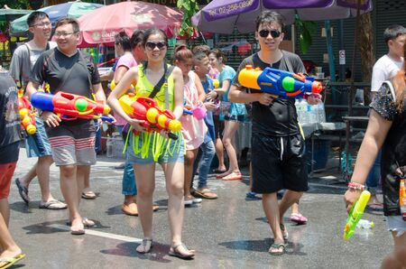 standoff: Bangkok, Thailand, 14 April 2015. A group of young partygoers getting ready to join the Songkran street party. The annual Songkran water festival is marked by splashing water on each other. Editorial