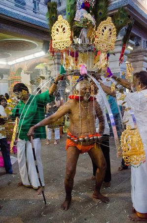 devotee: Singapore, 7 February 2012: An elderly Hindu devotee carries a kavadi during the annual Thaipusam festival.