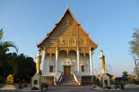 The ordination hall of Wat Pha That Luang in Vientiane, the most importat temples of Laos. The hall is decorated with carvings from Buddhas life. Stock Photo