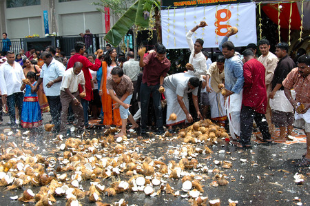 Georgetown, Penang, Malaysia - 7 February 2009: Devotees smashing coconuts on the ground to greet the impending arrival of the god Murugan.