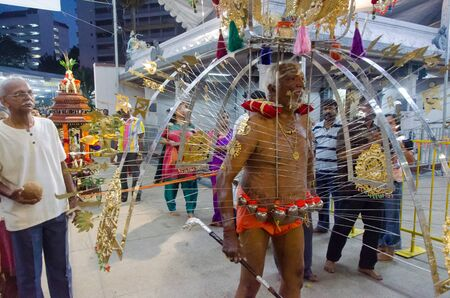 Singapore, Singapore - 7 February 2012: A elderly man carries and is skewered by the ceremonial kavadi, a decorated metal frame, as part of a thanksgiving ritual at the annual Thaipusam festival.
