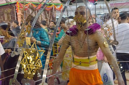 Singapore, Singapore - 7 February 2012: A man carries and is skewered by the ceremonial kavadi, a decorated metal frame, as part of a thanksgiving ritual at the annual Thaipusam festival. Editorial