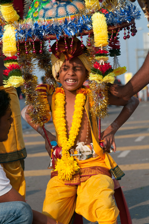 struggles: Kuala Lumpur, Malaysia - 20 January 2011: A young boy devotee struggles with carrying the ceremonial kavadi during Thaipusam. During the Hindu festival, devotees carry kavadis as part of a thanksgiving or supplication ritual. Editorial