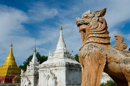 A statue of a lion stands guard over the ruins of Inwa, a former capital of Burma located in Mandalay Stock Photo