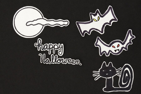 halloween message: a horizontal overhead view of a Halloween scene: cat, bats with a moon and clouds and a happy halloween message