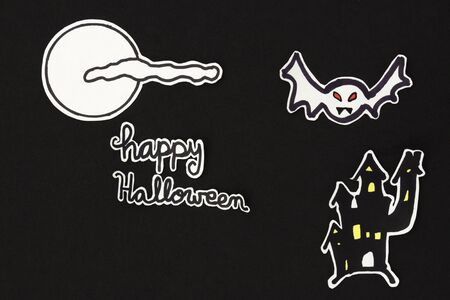 a horizontal overhead view of a Halloween scene: a house and a bat with a moon and clouds and a happy halloween message
