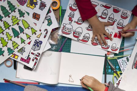 overhead: a horizontal overhead view of the hands of two little girls drawing Christmas decorations Stock Photo